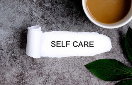 Self care with cup of coffee and green leaf