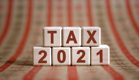 TAX 2021 text on wooden cubes on a monochrome background with reflection. Stock fotó
