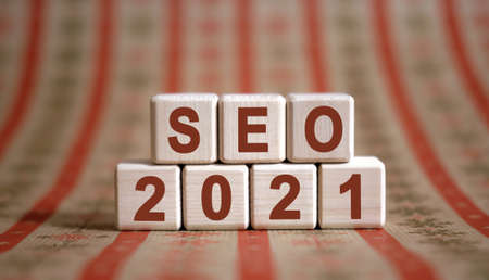 SEO 2021 text on wooden cubes on a monochrome background with reflection.