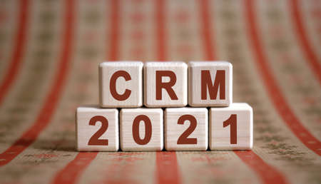 CRM 2021 text on wooden cubes on a monochrome background with reflection. Stock fotó