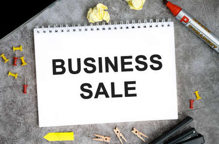 Business sale text on a white notebook with pins, marker and stapler on a concrete table