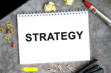 Strategy text on a white notebook with pins, marker and stapler on a concrete table