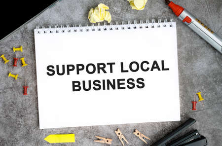 Support local businesses text on a white notebook with pins, marker and stapler on a concrete table Stock fotó