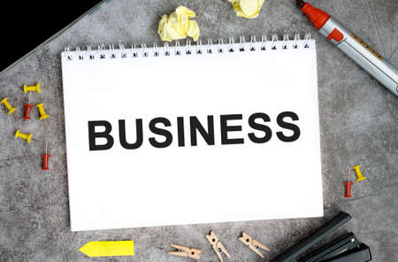 Business concept text on a white notebook with pins, marker and stapler on a concrete table