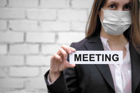 A European girl wearing a medical mask holds a sign with the inscription Meeting, against the backdrop of a white brick wall