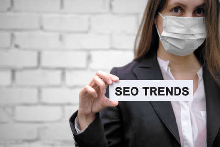 A European girl wearing a medical mask holds a sign with the inscription SEO trends, against the backdrop of a white brick wall
