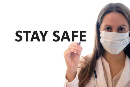 Stay safe from medic in a white robe and black protective gloves holds a stethoscope