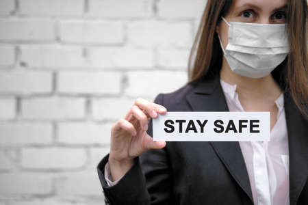 A European girl wearing a medical mask holds a sign with the inscription Stay safe , against the backdrop of a white brick wall 免版税图像