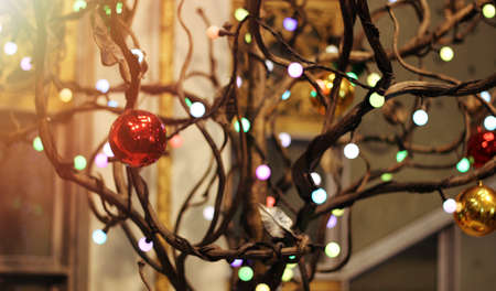 Decorative wood tree with illumination, light garland and colored balls for decoration 免版税图像
