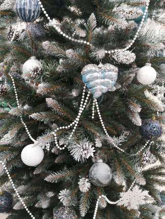 Snow-white branches of a christmas tree with christmas balls and garland
