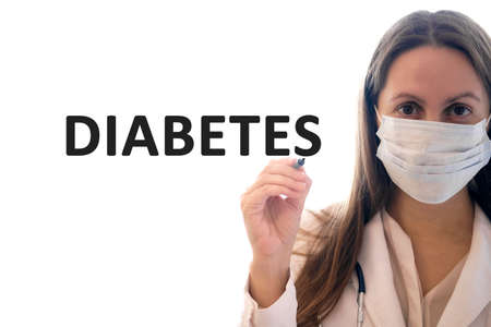 Doctor woman in a mask holds pen and writes Diabetes text