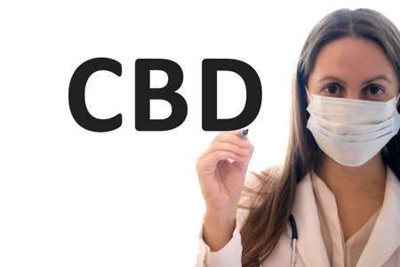 Doctor woman in a mask holds pen and writes CBD text
