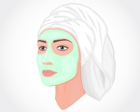 Close-up portrait of a beautiful young woman in half a turn isolated on white background with green cosmetic mask on her face and a towel on her head.