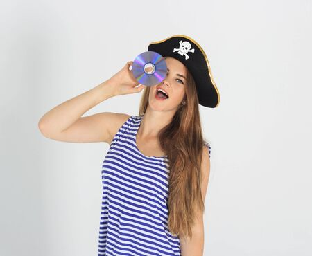mujer pirata: Nice young woman with pirate cd or dvd disk and hat with skull and crossbones. Concept of software piracy and copyrighting