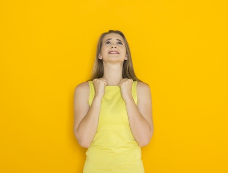 Excited young attractive woman. Funny impatient emotional girl. Studio shot orange background Stock Photo