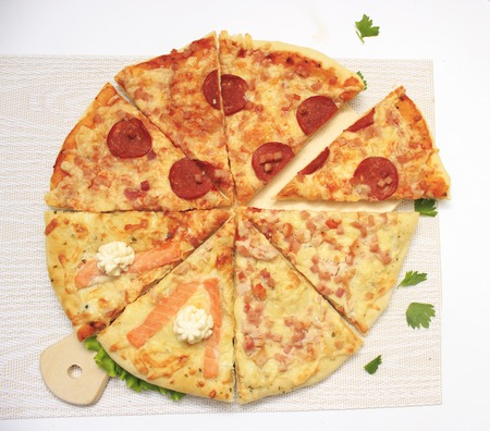Hot tasty homemade pizza with sausage, fish cheese and other ingredients in cut form is ready to eat on white background.