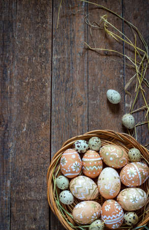 Painted Easter eggs in a nest on a dark rustic wooden background