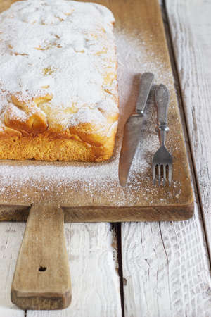 powdered: apple pie with powdered sugar on old wooden board
