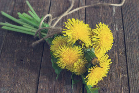 bouquet of yellow dandelions on the old wooden background toning photo