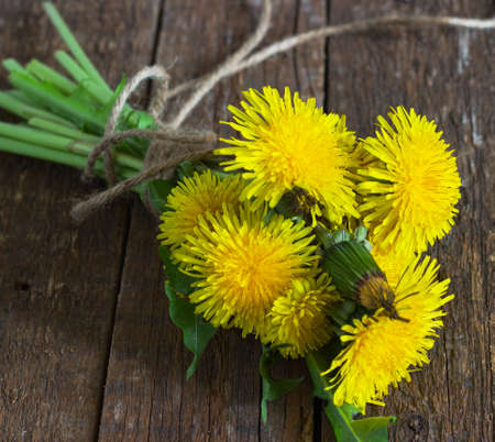 bouquet of yellow dandelions on the old wooden background photo