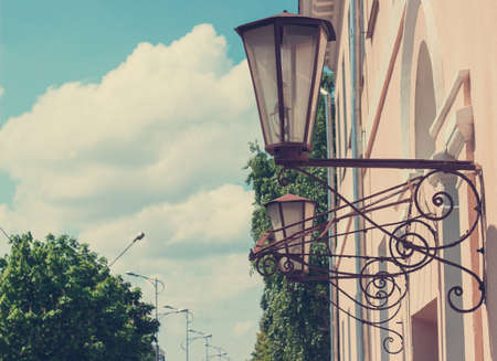 impasse: Street lamps on a building wall retro forging toning