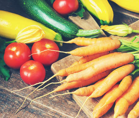 toned image: carrots, zucchini, tomatoes on a wooden background toned image