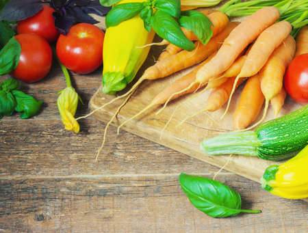 toned image: carrots, zucchini, tomatoes, basil on a wooden background toned image