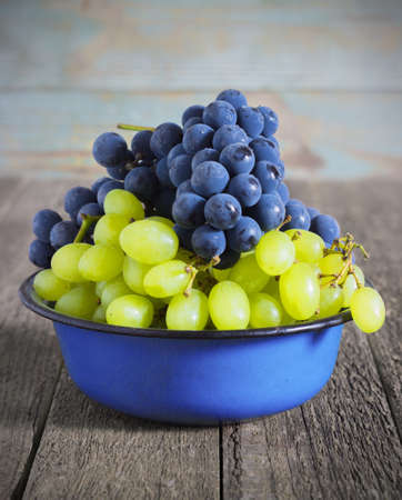 grape cluster: blue and green grapes in a metal bowl on a wooden background