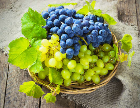 blue and green grapes in a basket on a wooden background toning Stockfoto