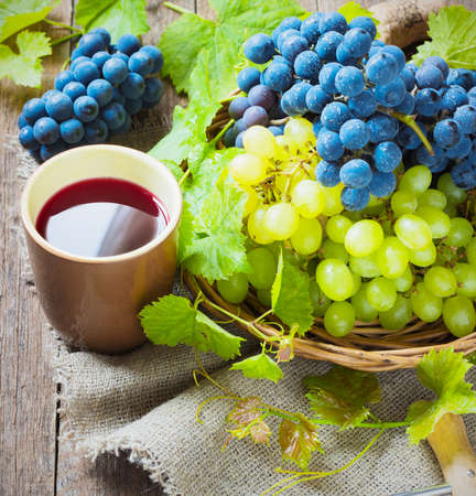 vins: red wine and grapes. Wine and grapes in vintage setting with corks on wooden table