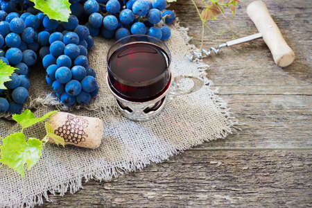 des vins: red wine and grapes. Wine and grapes in vintage setting with corks on wooden table