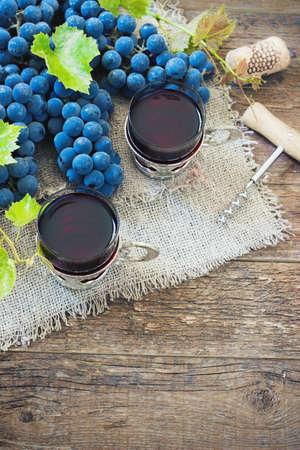 grapes: vino y las uvas rojas. Vino y uvas en el establecimiento de la vendimia con corchos en mesa de madera