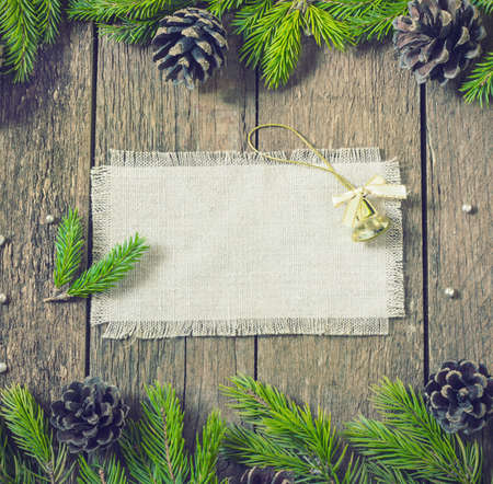 invitation: card frame with fir branches with New Years toys on a wooden background toning