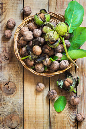 husks: Walnuts in green husks with leaves on a wooden background