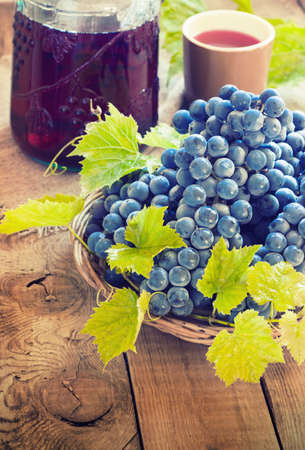 des vins: red wine and grapes. Wine and grapes in vintage setting on wooden table toning