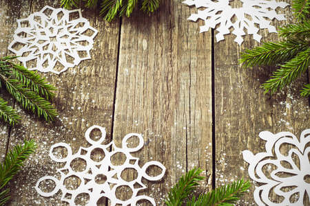 textured background: card frame with fir branches with New Years toys on a wooden background toning