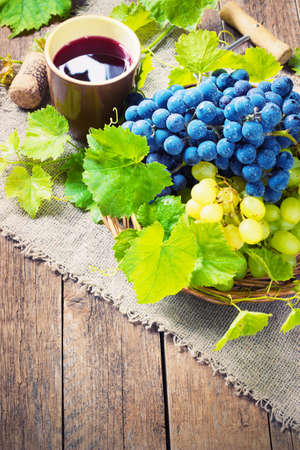 des vins: red wine and grapes. Wine and grapes in vintage setting with corks on wooden table toning
