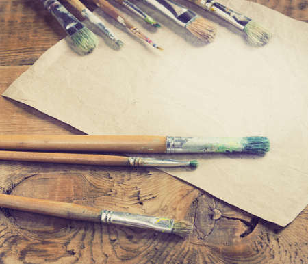 artist: Paint brushes for painting on a wooden background toning Stock Photo