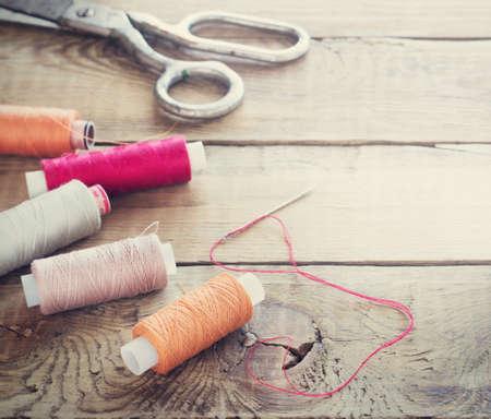 kit de costura: Tijeras, bobinas con hilo y agujas. herramientas de costura viejos en el fondo de madera vieja. tonificaci�n fondo de la vendimia
