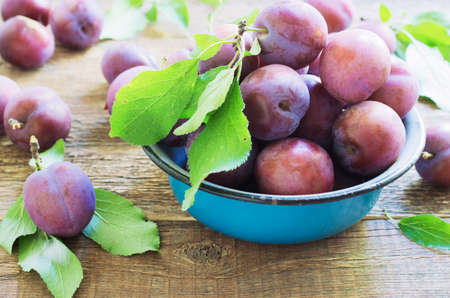 plums on a wooden rustic table in a metal bowl. Stock Photo