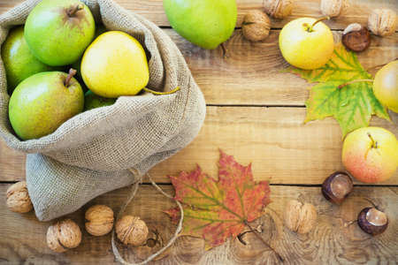 Autumn composition of fruits, nuts and spices - pears, walnuts, maple leaves on a wooden background