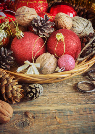Cristmas: Christmas Composition red and yellow balls, cones, nuts in a basket on a wooden background.Vintage style. toning Stock Photo