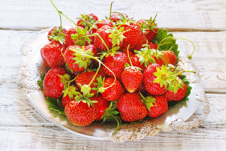 vitamine: Fresh and delicious organic strawberries on old metal plate, wooden table. Perfect for your healthy eating dieting.