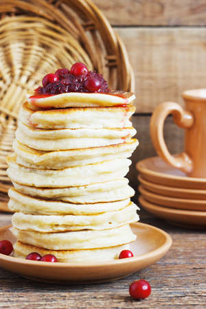 Stack of delicious pancakes with cranberries on plate and napkin on wooden background rustic