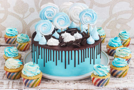 curlicues: Childrens blue cake and cupcakes rainbow color on a white background with wood meringue