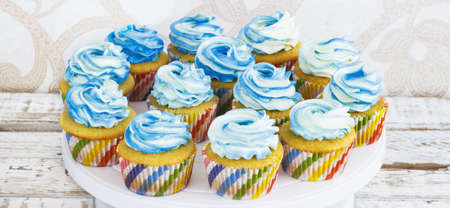 Festive cupcakes with cream in blue on a white wooden background.