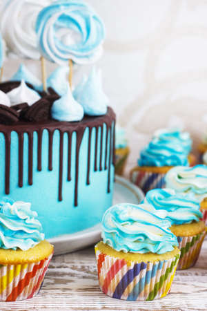 Festive cupcakes and cake with cream in blue on a white wooden background.