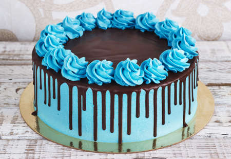 curlicues: Birthday cake with cream chocolate drips on a white background.