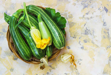 Fresh zucchini on wicker mat on Light background with a flower