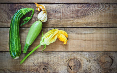 phallic: Fresh zucchini on wooden background with a flower Stock Photo